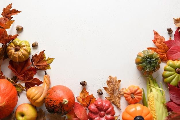季節の収穫、カボチャ、テキスト用のスペースと白い背景の上のカラフルな葉。秋の構成。ハロウィーンや感謝祭の日の概念。