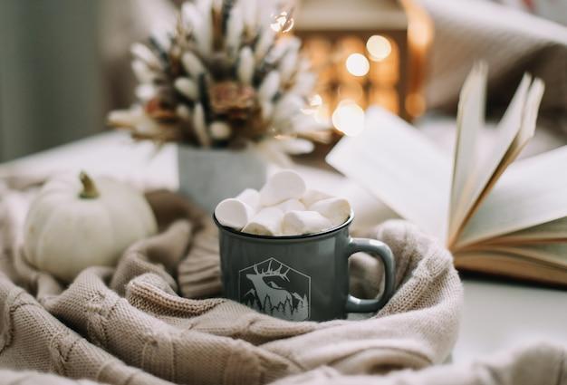 Сезонное украшение дома осенью с чашкой кофе, засушенными цветами, белой тыквой и книгой