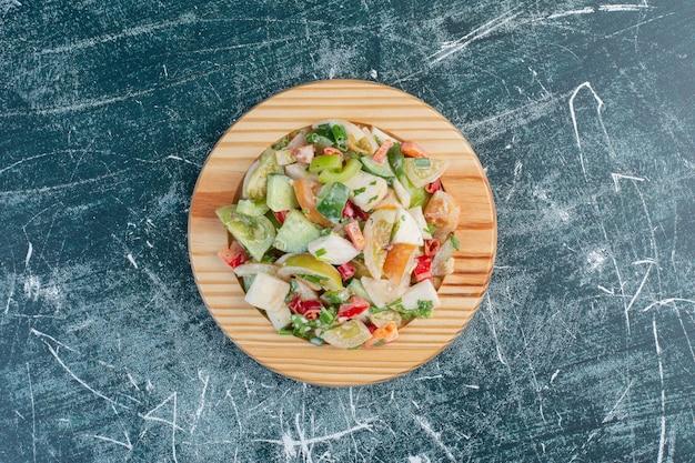Insalata di stagione con ingredienti misti su un piatto di legno.