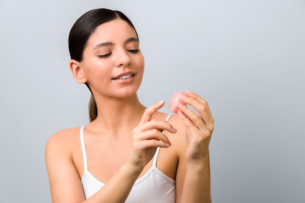 Seasonal skin protection. smile woman applying lip protection balm against grey wall