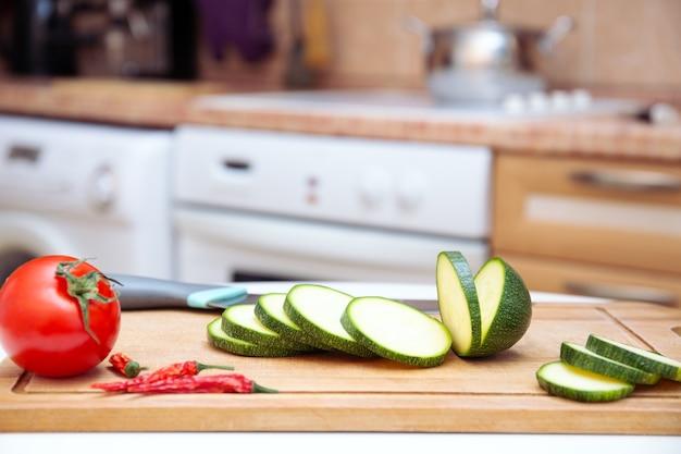Сезонные кабачки или кусочки кабачков на деревянной разделочной доске. готовим овощи для гриля, для ресторана. предпосылка кухни, предпосылка еды. здоровая веганская диета или вегетарианская пища.