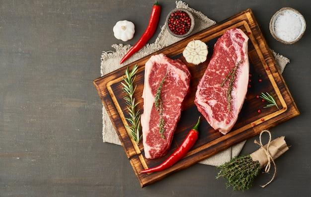 Seasoning raw steak with salt, thyme, garlic. two big whole piece of raw beef meat
