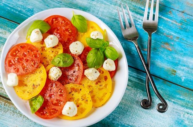 Приправить нарезанный помидор моцареллой, базиликом на тарелке вилкой. вид сверху.