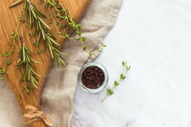木製のサービングボードにコショウ豆とスパイスハーブを入れた肉の小さな瓶の調味料