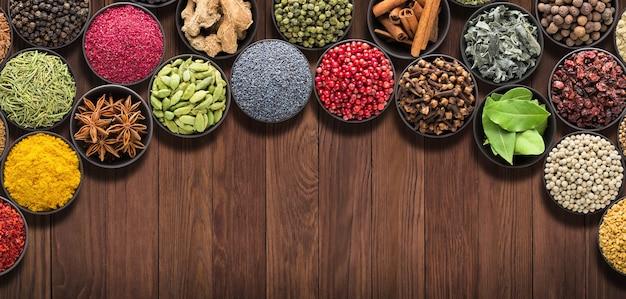 木製テーブルの調味料スパイスとハーブの背景