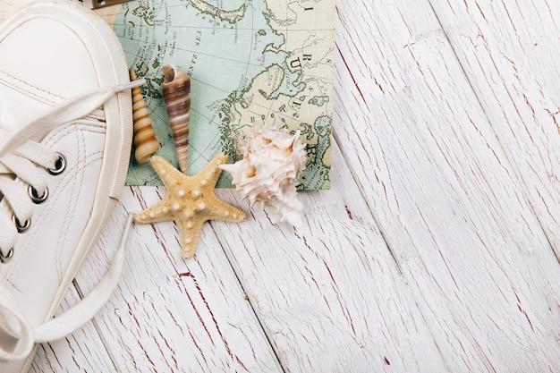 Seastars lie behind white keds on travel map