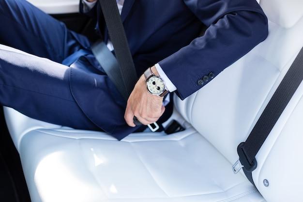 Ремень безопасности. крупным планом бизнесмена в ручных часах и темном костюме, крепящем ремень безопасности