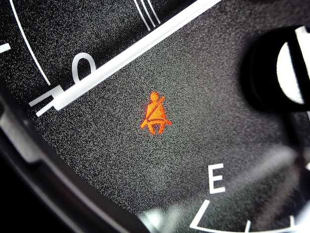 Seat belt warning light illuminates on the instrument panel in the car.