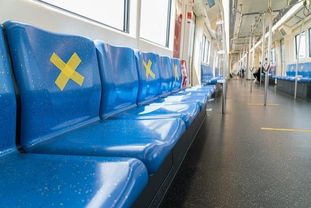 사회적 거리를두기 위해 앉지 않기 위해 노란색 십자가가있는 기차 지하철 좌석