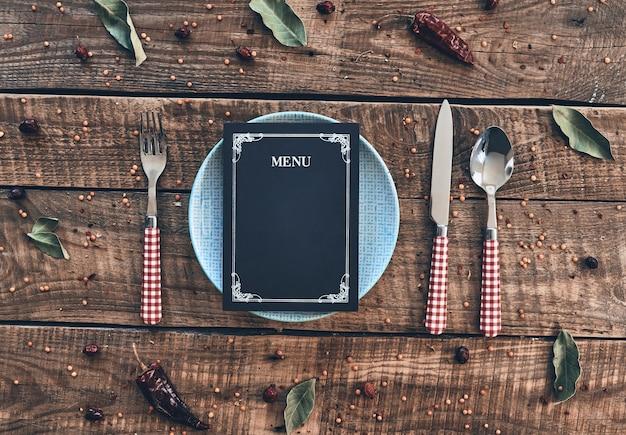 Место зарезервировано. выстрел под большим углом: пустая тарелка, вилка, ложка, нож и закрытое меню