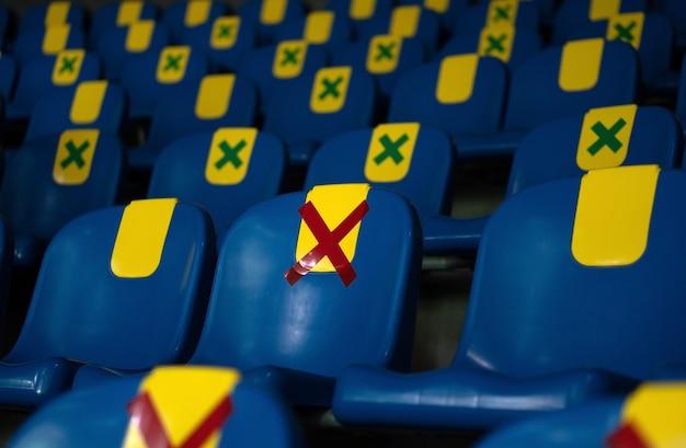 Сиденье с наклейкой с красным символом размещено на стуле в общественных местах, чтобы одно сиденье находилось на расстоянии от других людей.