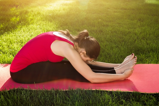 Seated forward bend pose. woman practicing yoga sitting on mat in park