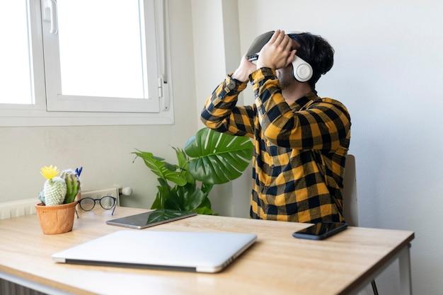 Сидящий мужчина работает в домашнем офисе в очках виртуальной реальности