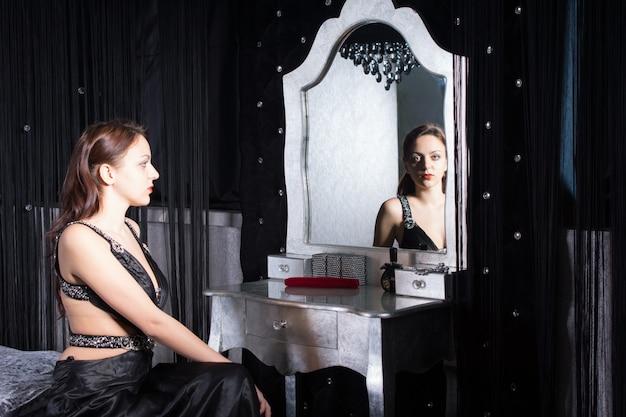 Сидящая красотка в элегантном черном платье перед зеркалом в своей комнате.