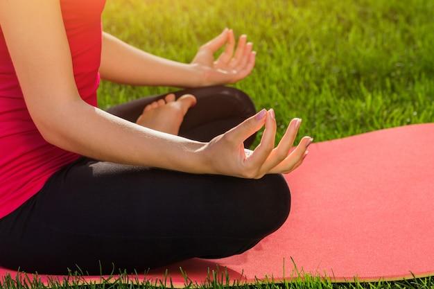 着席ヨガのポーズ。ヨガの練習。女性は夏の公園で瞑想します