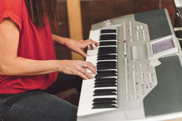 전자 피아노를 연주하는 앉아있는 젊은 여성