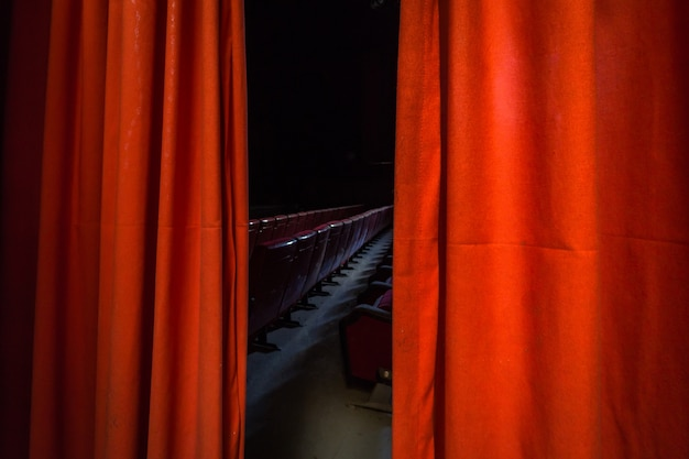 Seating of a cinema seen from the red curtain