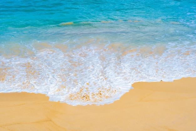 Seawater waves splash on sandy beach