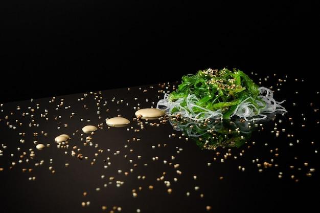 Морские водоросли и лук с кунжутом на черном фоне с отражением