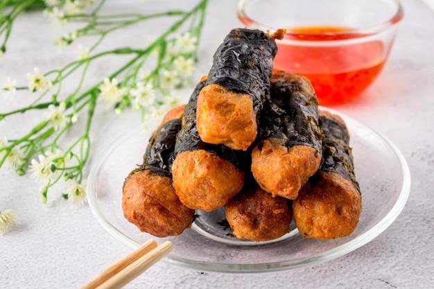 Куриный рулет из морских водорослей укладывается на стеклянную тарелку с палочками для еды и сладким соусом чили.