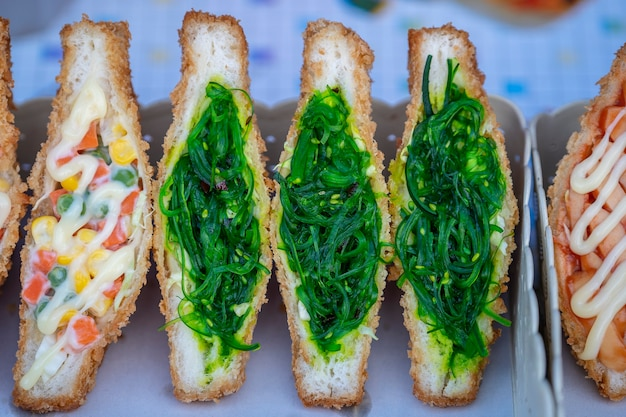 タイのパンガン島の屋台の食べ物市場で販売されている海藻サラダサンドイッチ。おいしい緑の海藻サラダサンドイッチをクローズアップ