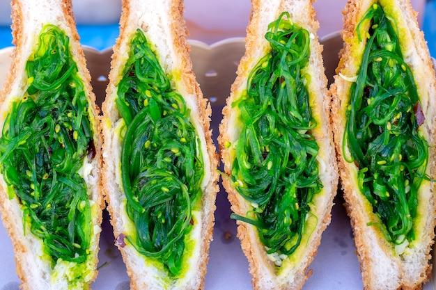Сэндвич с салатом из морских водорослей для продажи на рынке уличной еды