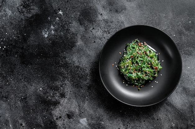 The seaweed salad with sesame seeds. black background. top view. copy space