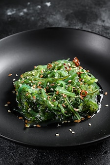 The seaweed salad with sesame seeds. black background. top view