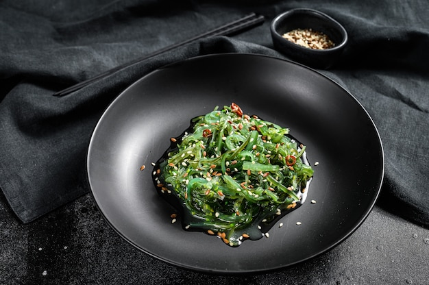 Seaweed salad with sesame seeds in a plate with chopsticks. black background. top view