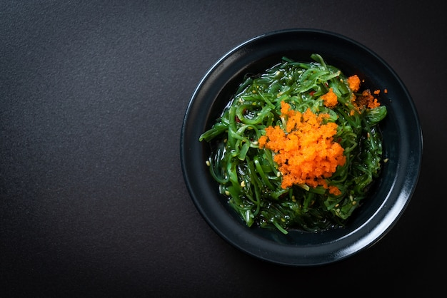 Seaweed salad with shrimp eggs - japanese style, copyspace background
