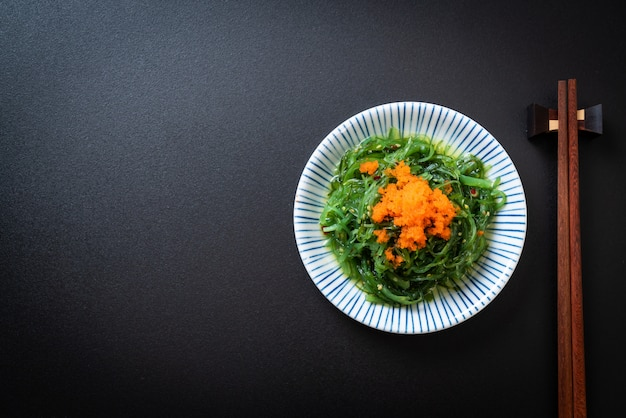 Seaweed salad with shrimp eggs - japanese style, copyspace black background