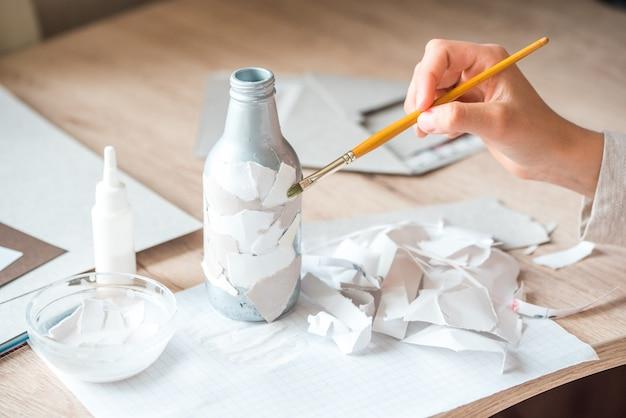 Вторичное использование бумажного мусора. детская ручная работа из папье-маше. руки ребенка приклеены к кусочкам бумаги на бутылочке.