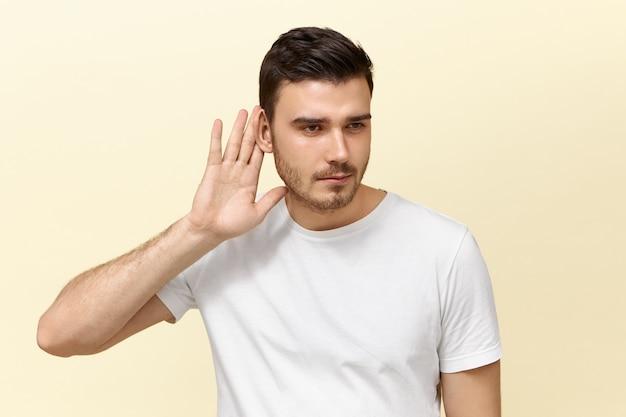 Концепция секретности и заговора. изолированное изображение любопытного любопытного красивого молодого парня с щетиной, держащей руку в ухе, с любопытным взглядом, подслушивания, попытки подслушать частный разговор