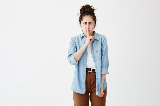 Secrecy, privacy and confidentiality. frowning woman with hair in bun in denim shirt and serious strict look holding index finger on her lips, saying shh, demanding silence or asks to keep secret