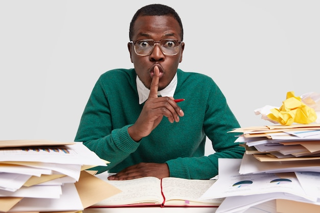 Secret african american male ceo shows silence sign, works on task recieved from boss, writes down ideas in notebook, has surprised facial expression