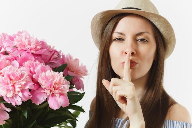Секретная девушка. женщина говорит, тишина, тише с пальцем на губах, шшш жестом с букетом цветов розовых пионов, изолированных на белом фоне. концепция праздника святого валентина или международного женского дня