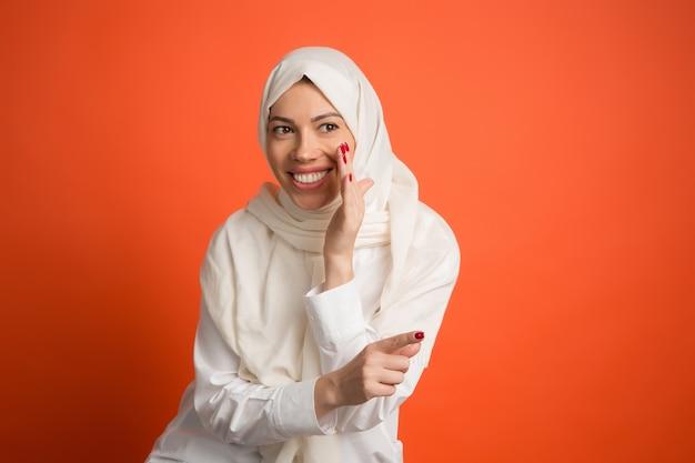 秘密のゴシップコンセプト。ヒジャーブの幸せなアラブの女性。赤いスタジオの背景でポーズをとって、笑顔の女の子の肖像画。若い感情的な女性。人間の感情、表情のコンセプト。正面図。
