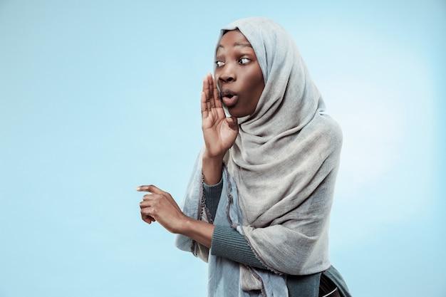 비밀, 가십 개념입니다. 그녀의 손 뒤에 비밀을 속삭이는 젊은 아프리카 여성. 트렌디한 파란색 스튜디오 배경에서 격리된 여자입니다. 젊은 감정적인 여자. 인간의 감정, 표정 개념입니다.