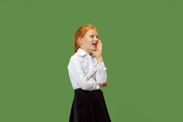 秘密のゴシップコンセプト。彼女の手の後ろに秘密をささやく少女。彼女はトレンディな緑のスタジオの背景に孤立しました。若い感情的なティーン。人間の感情、表情の概念。