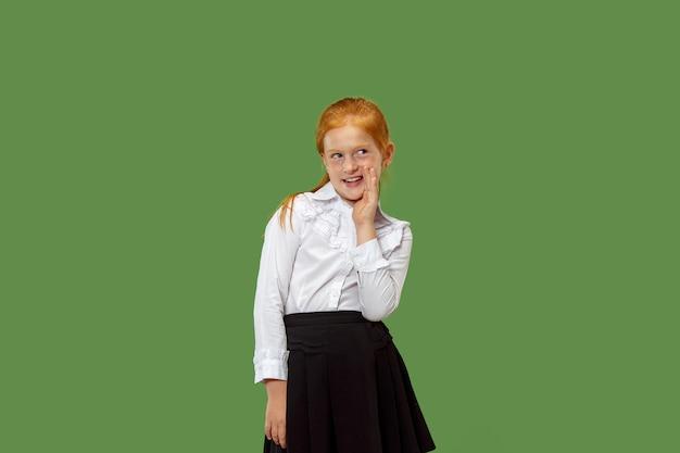 Segreto, concetto di gossip. ragazza che bisbiglia un segreto dietro la sua mano. ha isolato su sfondo verde alla moda per studio. giovane adolescente emotivo. emozioni umane, concetto di espressione facciale.