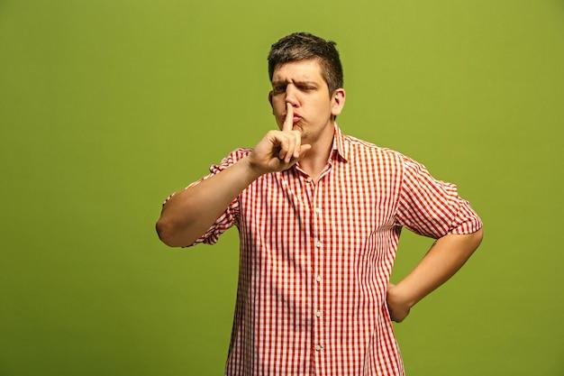 비밀, 가십 개념. 그의 손 뒤에 비밀을 속삭이는 젊은 남자. 유행 녹색 스튜디오 배경에 고립 된 사업가입니다. 감정적 인 젊은이.