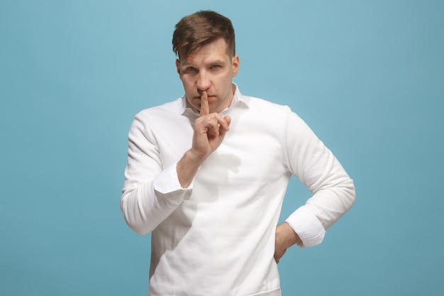 Secret, gossip concept. young man whispering a secret behind his hand. businessman isolated on trendy blue studio background. young emotional man. human emotions, facial expression concept.
