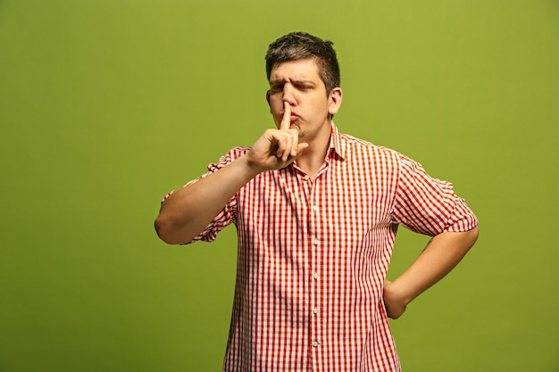 Segreto, concetto di pettegolezzo. giovane che bisbiglia un segreto dietro la sua mano. uomo d'affari isolato su sfondo verde alla moda per studio. giovane uomo emotivo.