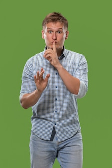 Secret, gossip concept. young man whispering a secret behind his hand.