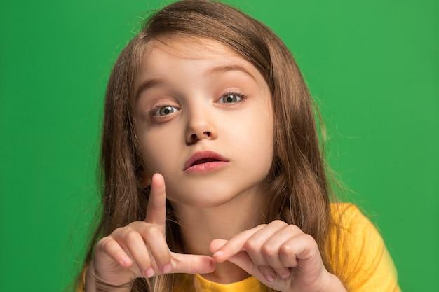 비밀, 가십 개념. 유행 녹색 스튜디오 배경에 고립 된 그녀의 손 뒤에 비밀을 속삭이는 어린 십대 소녀