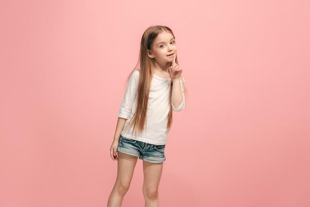 秘密のゴシップコンセプト。トレンディなピンクのスタジオの背景に分離された彼女の手の後ろに秘密をささやく若い十代の少女。若い感情的な女の子