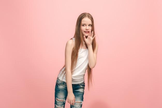 秘密のゴシップコンセプト。トレンディなピンクのスタジオの背景に分離された彼女の手の後ろに秘密をささやく若い十代の少女。