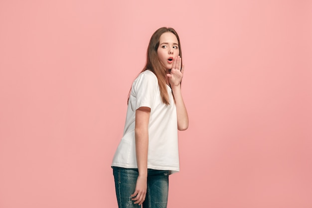 Secret, gossip concept. young teen girl whispering a secret behind her hand isolated on trendy pink. young emotional girl