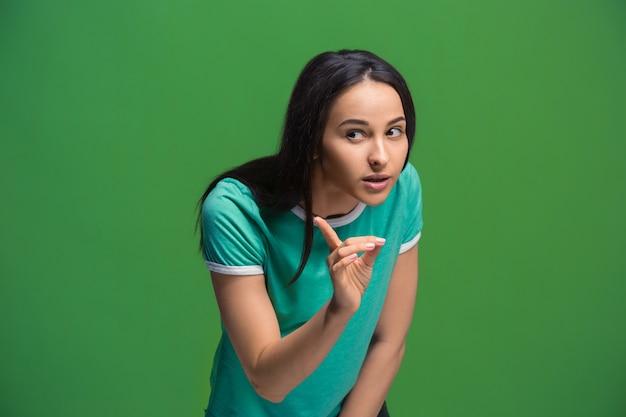 Секрет, концепция сплетен. молодая женщина шепчет секрет за ее рукой. деловая женщина, изолированные на модном зеленом фоне студии. молодая эмоциональная женщина. человеческие эмоции, концепция выражения лица.