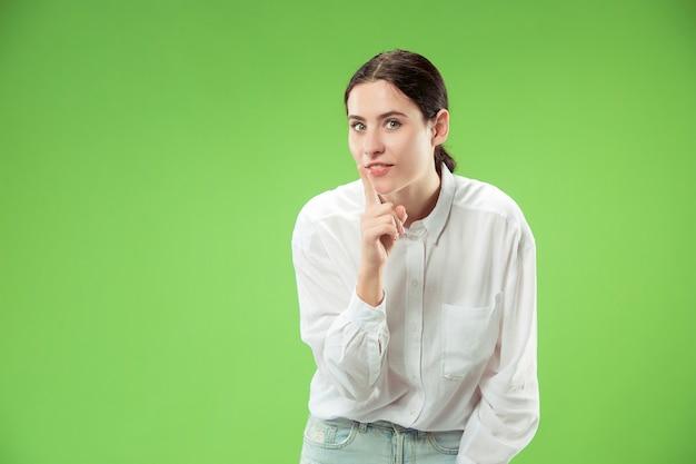 비밀, 가십 개념. 그녀의 손 뒤에 비밀을 속삭이는 젊은 여자. 유행 녹색 스튜디오 배경에 고립 된 비즈니스 우먼입니다. 젊은 감정적 인 여자. 인간의 감정, 표정 개념.